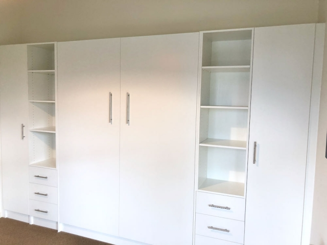 Wall bed closed with cupboards and shelves